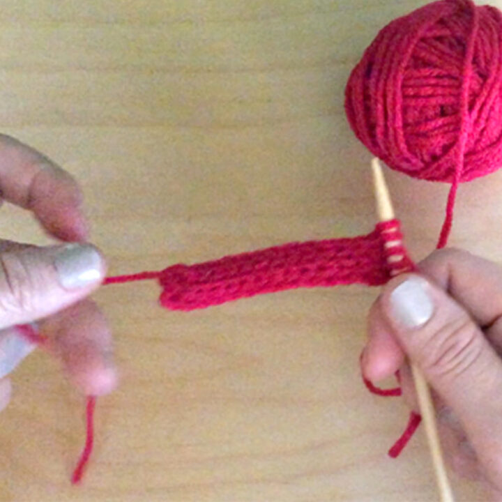 Hands knitting an i-cord with pink yarn and one knitting needle.