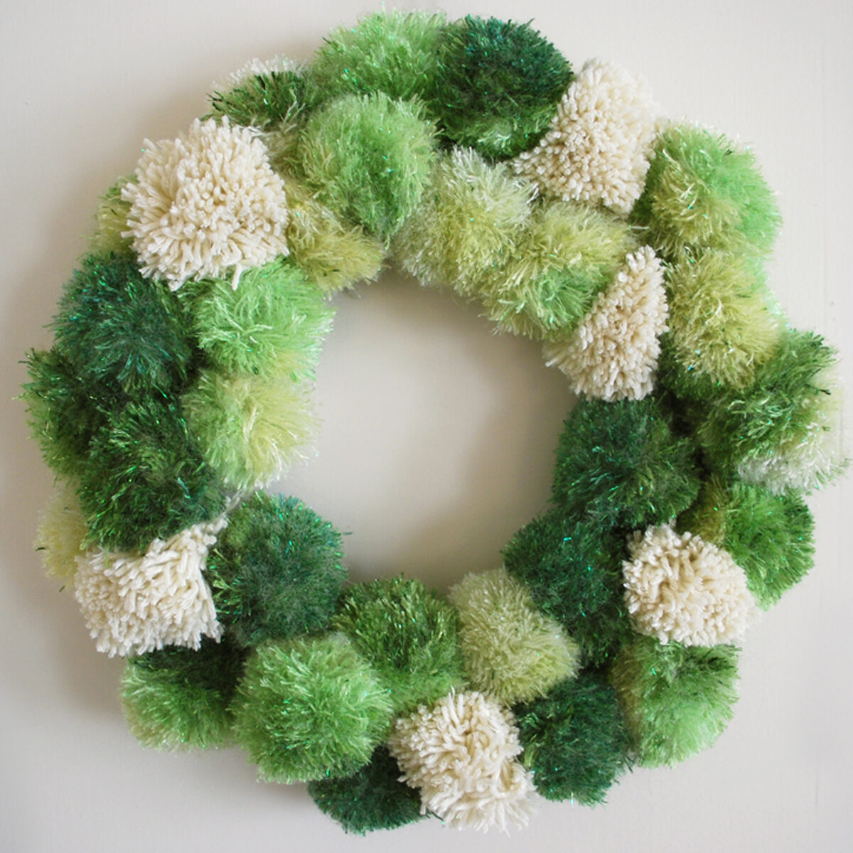 Yarn Pom Poms in wreath shape in green shades and white color.