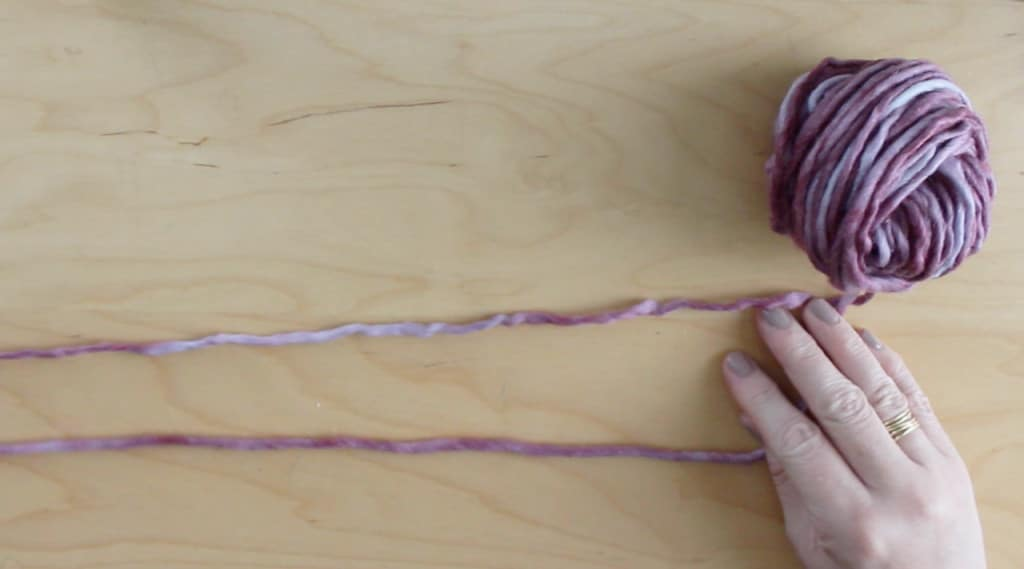 Hands with purple yarn strands on a table