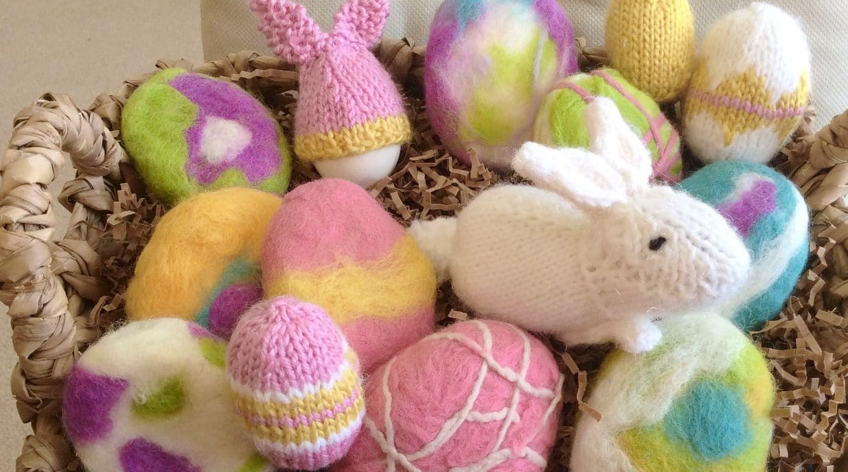 A group of felted soap and stuffed knitted bunny and easter eggs in a basket