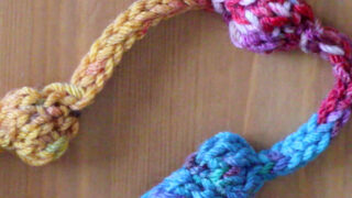 Knitted necklace with beaded texture in yellow, pink, and blue color yarn.