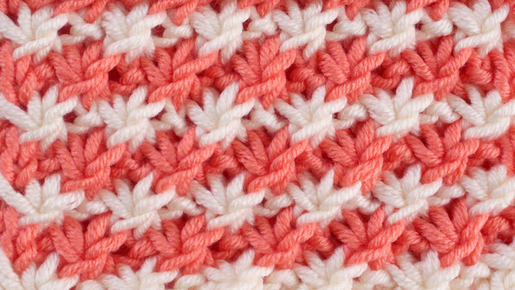 Close up a swatch of Daisy Stitch in orange and white yarn