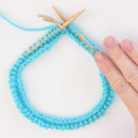 Circular Knitting Needle with blue color yarn cast on and woman's hand