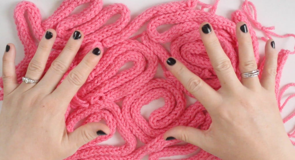 Hands and knitted icords in pink yarn