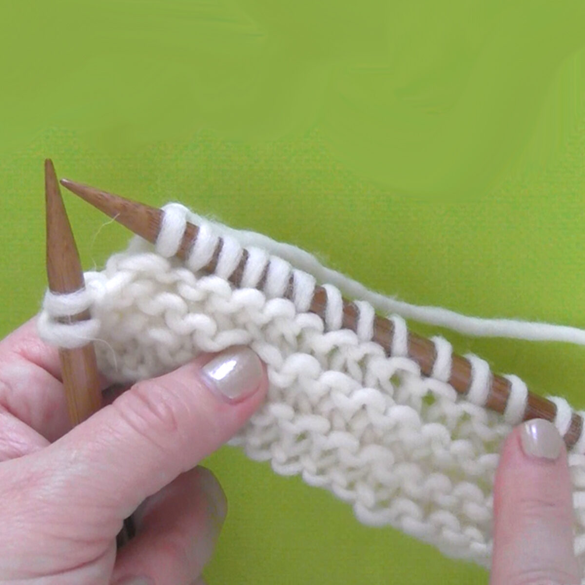 knitted swatch of garter stitch on knitting needles in white color yarn held by hands.