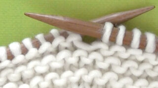 Garter Stitch Knitted Pattern cast on knitting needles in white yarn atop a green background.