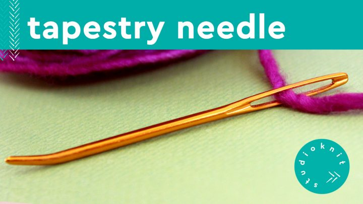 Gold tapestry needle threaded with magenta yarn