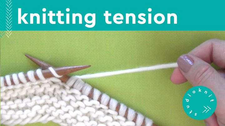 Hand demonstrating knitting tension with white yarn and knitting needles