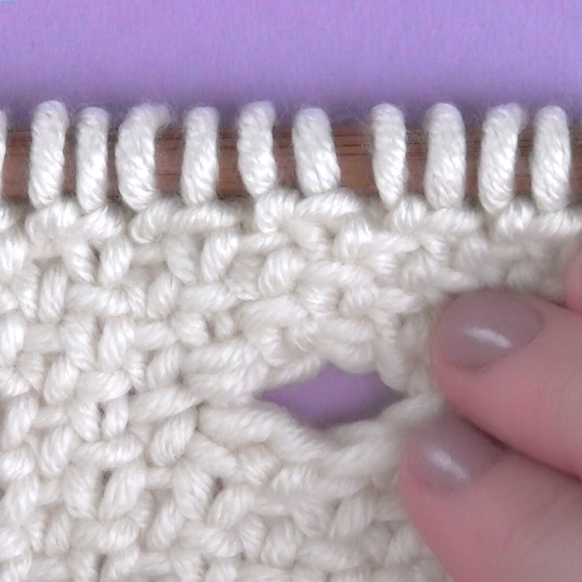 Knitted swatch in white yarn with buttonhole opening on a knitting needle with woman's hand.