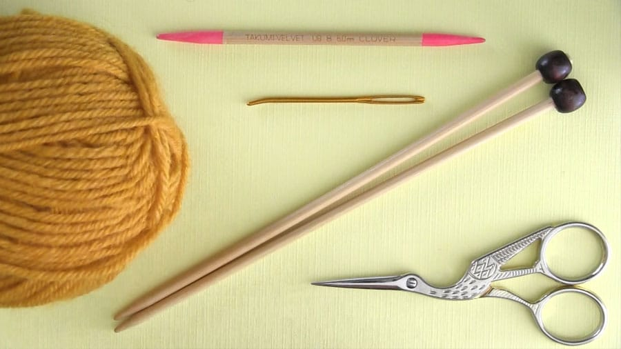 Knitting materials with yellow yarn, knitting needles, a tapestry needle, and scissors.