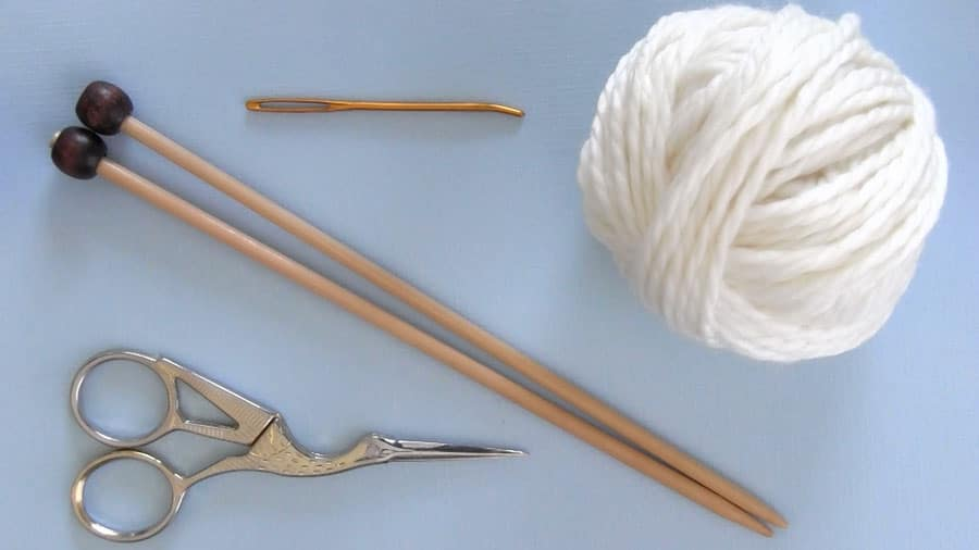 Stitch pattern materials and tools of white yarn, straight knitting needles, tapestry needle, and scissors