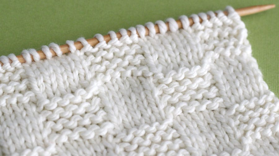 Side view of Close swatch of textured Garter Checkerboard Stitch in white yarn on a knitting needle