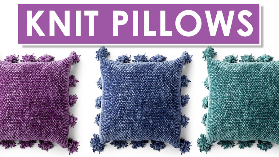 Three knitted pillows in velvet yarn in colors purple, blue, and green colors edged with pompom tassels