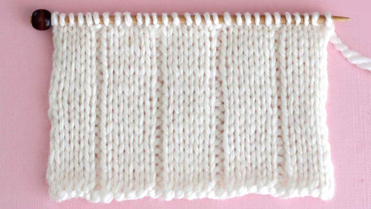 Close up a swatch of textured 5x1 Rib Stitch in white yarn on a knitting needle