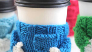 Knitted Coffee Cozy in sweater shape with blue yarn color.
