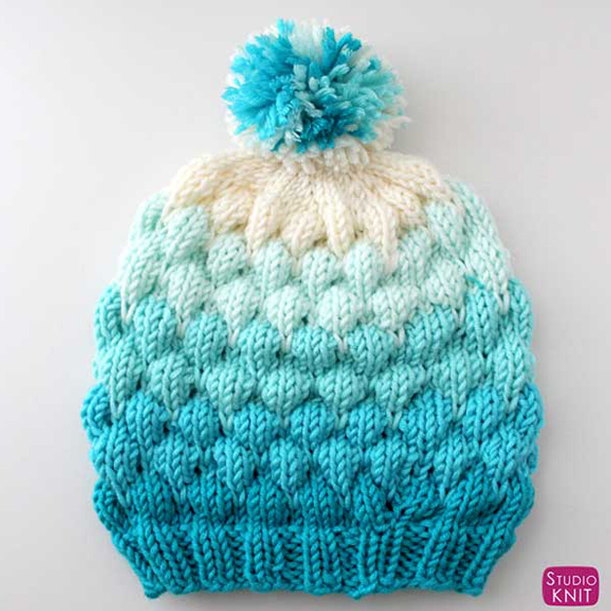 Knitted Bubble Beanie Hat in shades of blue yarn color with pom pom.