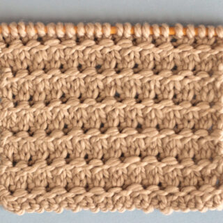Knitting Swatch in the Granite Stitch Pattern texture in light brown yarn on a wooden bamboo knitting needle.