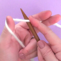 Hands demonstrating how to cast on without a slip knot with white yarn and wooden bamboo knitting needles atop a purple background.