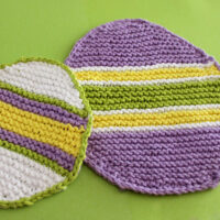 Two knitted Easter Egg Dishcloths in purple, white, yellow, and green stripes atop green backdrop.
