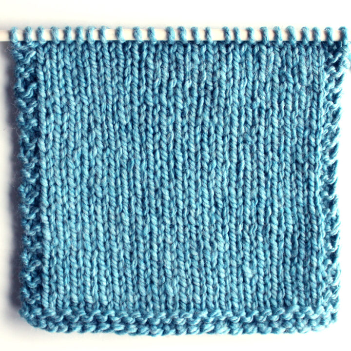 Stockinette Knit Stitch Pattern in blue color yarn on needle.