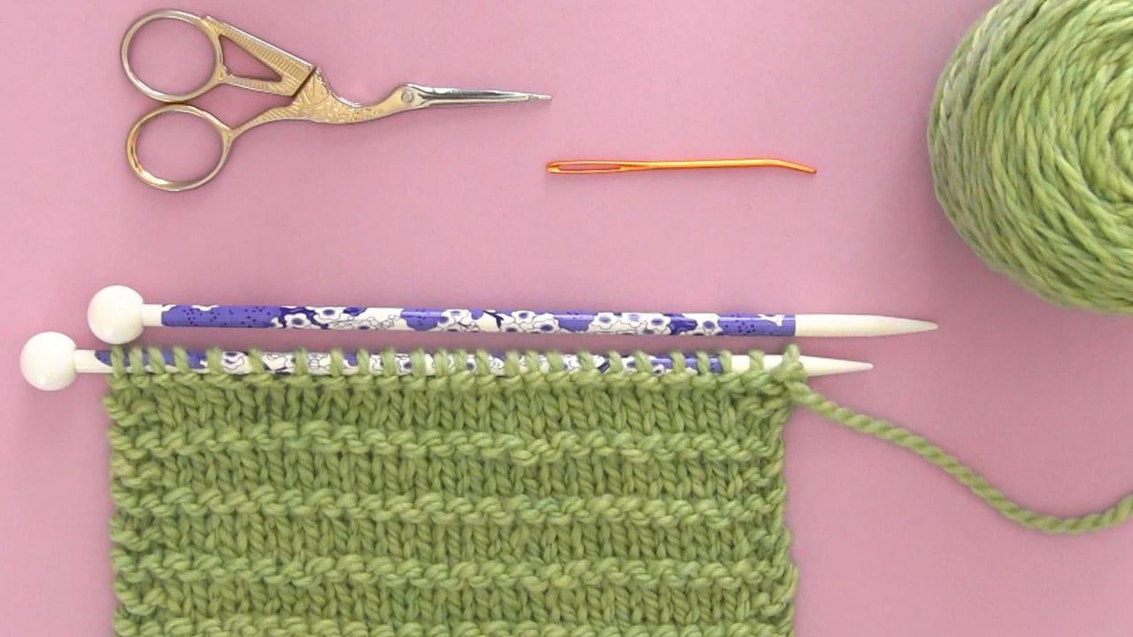 Strickmaterial Garn, Stricknadeln, Schere und Gobelin-Nadel