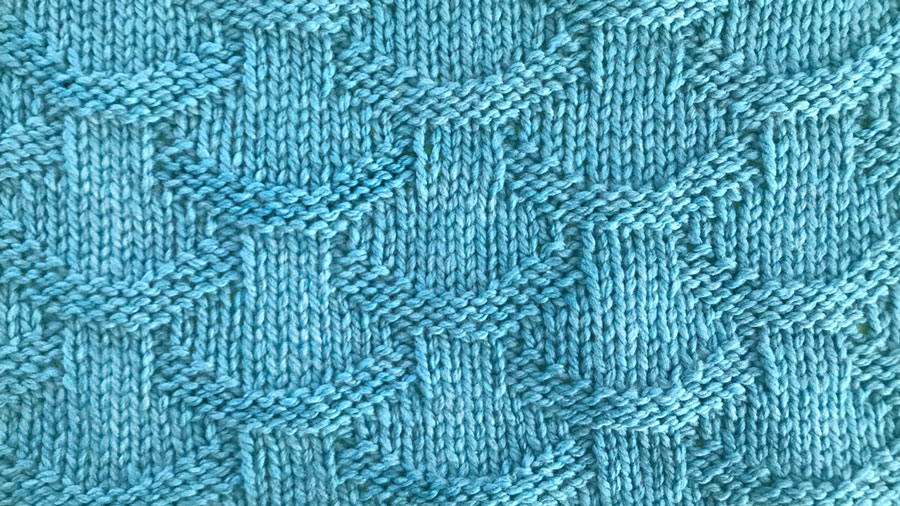 Close up a swatch of textured Basket Loop Stich in blue yarn