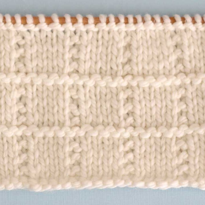 A close up of Tile Square knitted swatch in white yarn on straight knitting needle