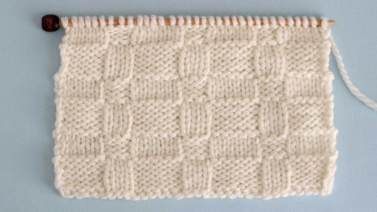 Close up a swatch of textured Wide Basket Weave Stich in white yarn on a knitting needle