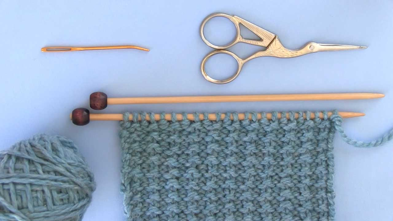 Materials to Knit Sand Stitch Pattern yarn, knitting needles, scissors, and tapestry needle