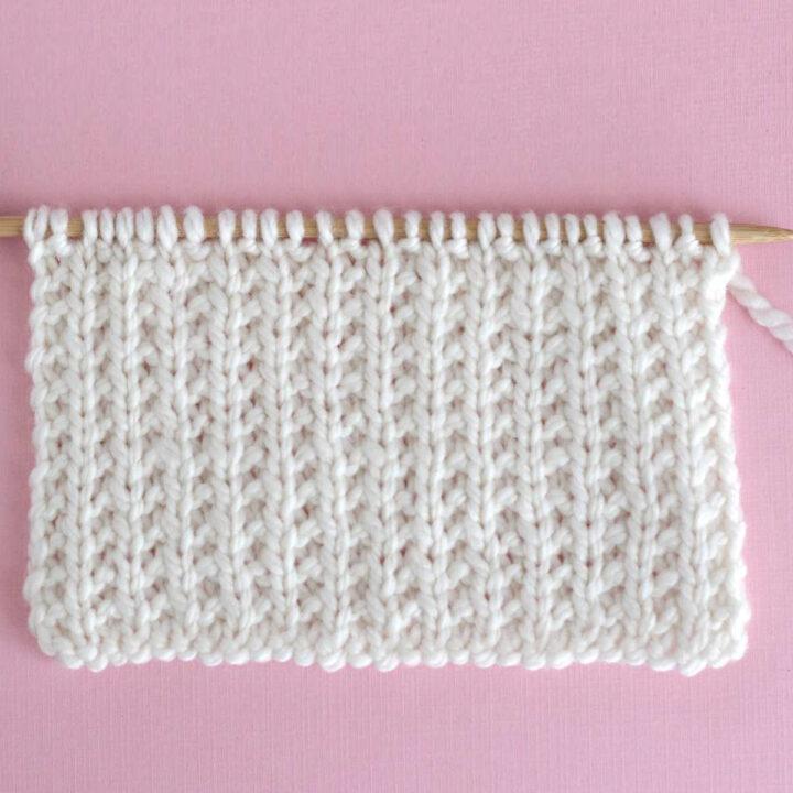 Broken Rib Knit Stitch Pattern in white color yarn on knitting needle.
