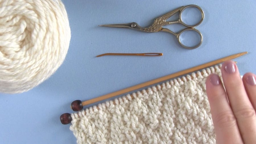 Knitting Materials for Chevron Rib Stitch with yarn, knitting needles, scissors, and tapestry needle