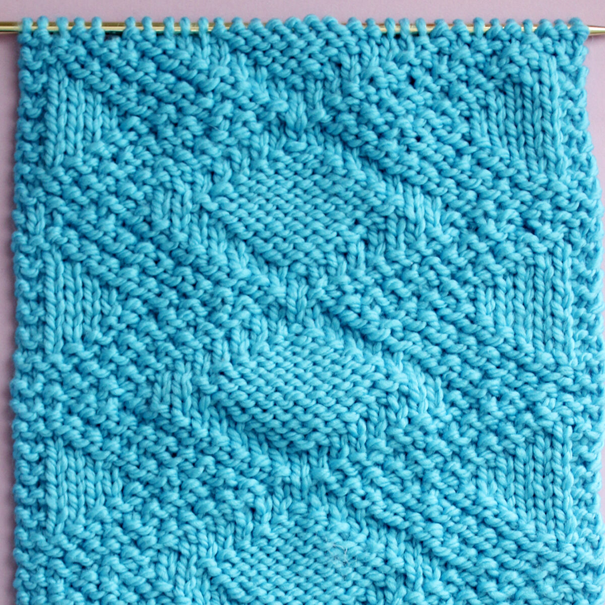 Knitted Swatch of the Fancy Diamond Knit Stitch Pattern texture in blue color yarn on a straight knitting needle.