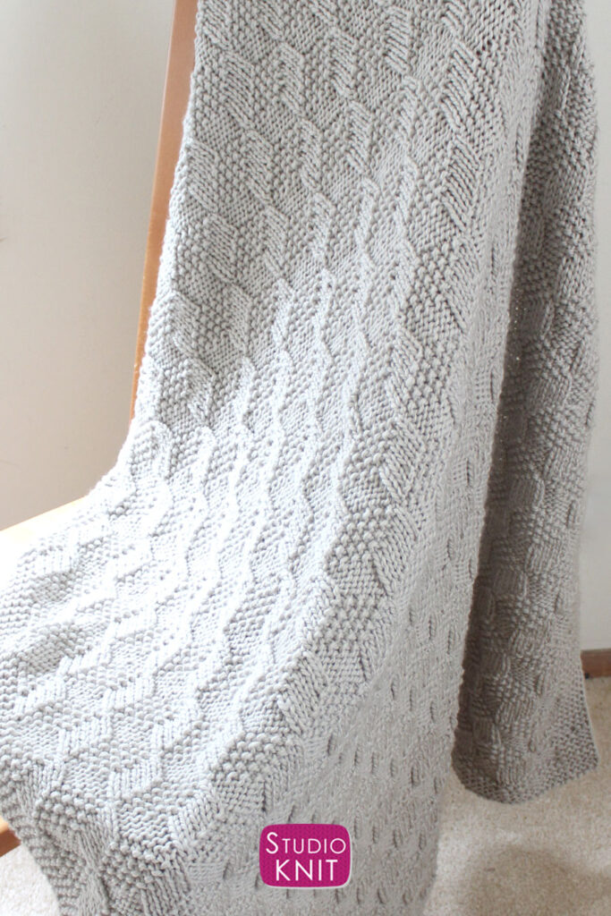 Knitted Blanket in Tumbling Moss Blocks Stitch draped over wooden chair