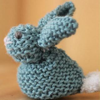 Knitted bunny softie in garter stitch with blue yarn.