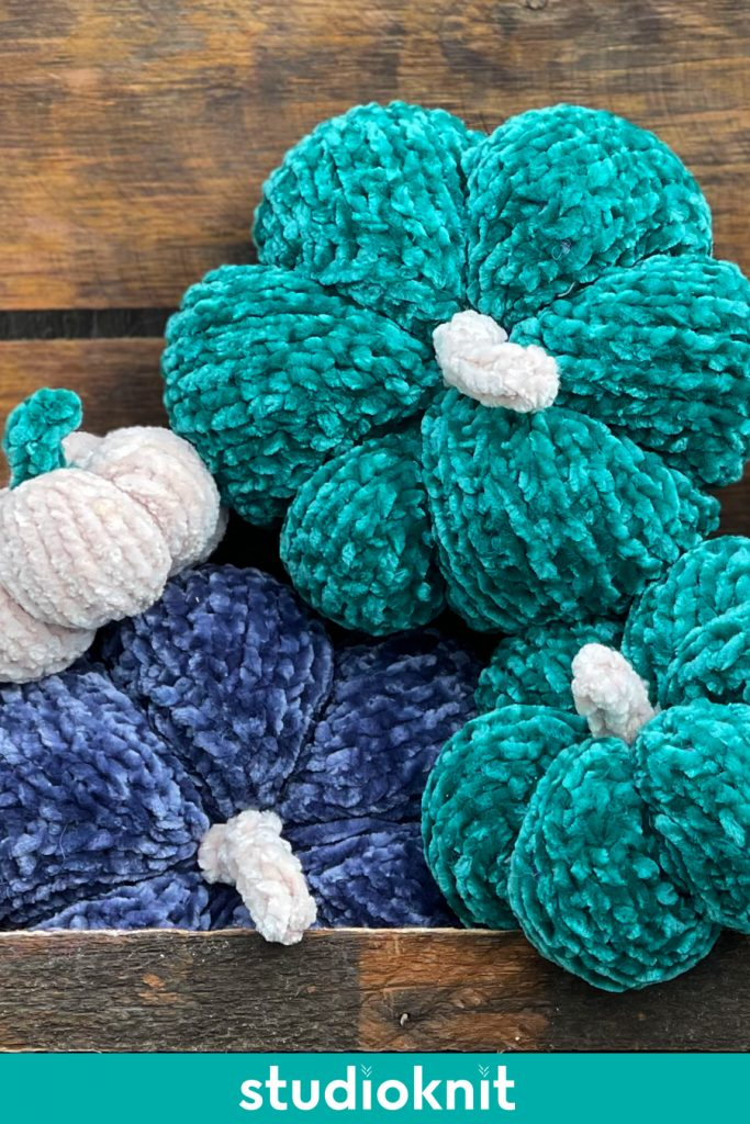 Velvet knitted pumpkins stacked atop each other in blue, green, and white yarn colors