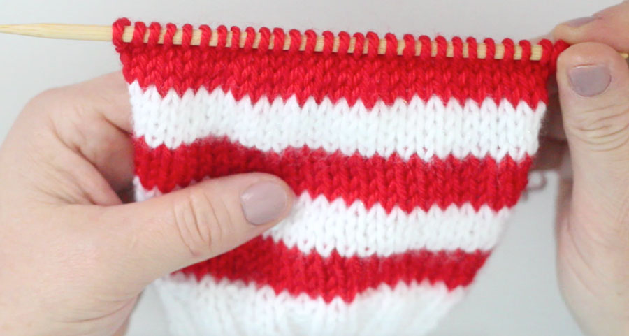 Red and White stripe knitting piece on a knitting needle in the Stockinette Stitch