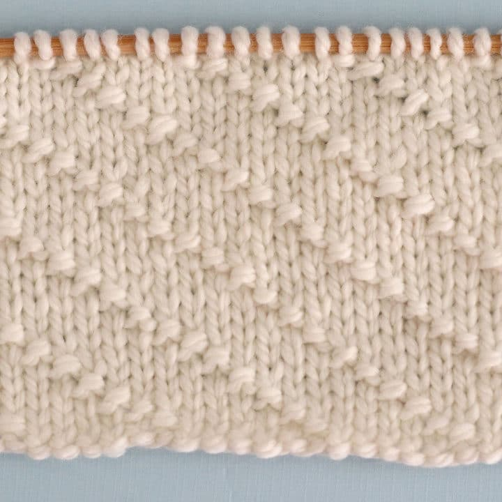 Swatch of textured Diagonal Seed Stitch swatch in white yarn on a knitting needle