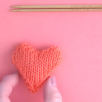 Knit Heart in orange yarn color with hand and knitting needles