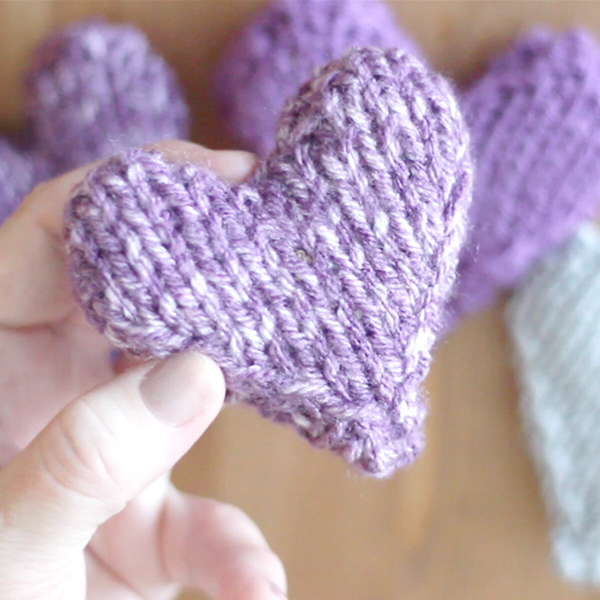 puffy stuffed knitted heart with hand holding