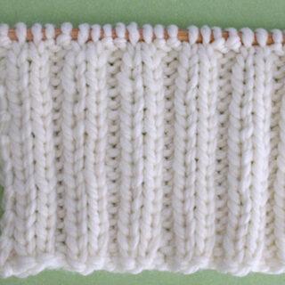 2x2 Rib Stitch Knitting Pattern in white yarn on knitting needle