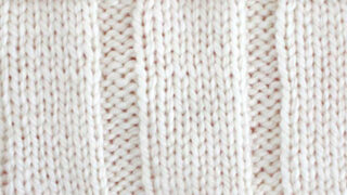 7x3 Rib Knit Stitch Pattern in white yarn on knitting needle.