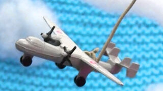 Toy airplane over swatch of knitted garter stitch blanket in blue yarn color with poly-fill clouds.