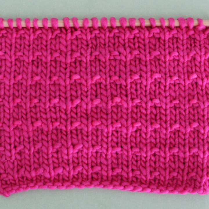 Andalusian Knit Stitch Pattern texture in pink color yarn on knitting needle.