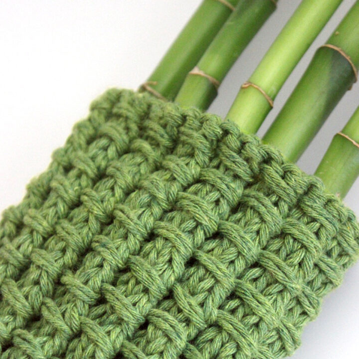 Knitted Bamboo Stitch Pattern swatch in green color yarn wrapped around bamboo stalks.
