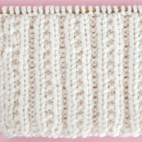 Beaded Rib Knit Stitch Pattern in white color yarn on knitting needle.
