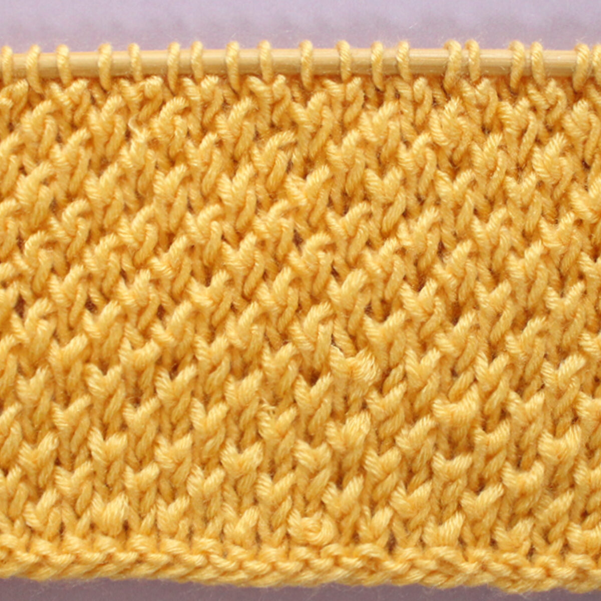 Bee Stitch Knitting Pattern texture in yellow color yarn on knitting needle.