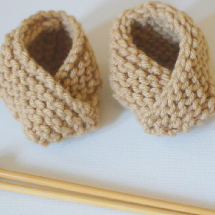 Knitted baby booties in garter stitch with beige yarn color and knitting needles.