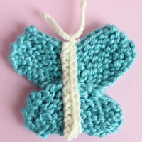 Knitted butterfly shape in blue color yarn atop a pink background.