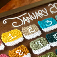 Knitted swatches inside a glass frame to create a calendar with numbers on each.