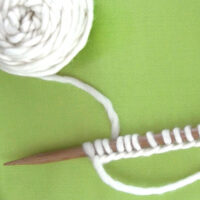 Knitting Stitches Cast On Knitting Needle with white color yarn.